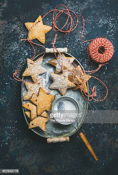 Christmas holiday star shaped gingerbread cookies for Christmas tree decoration, sieve, decorative snowflakes, balls and toys in metal tray over dark blue background,
