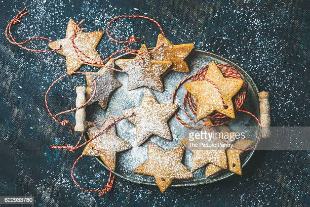Christmas holiday star shaped gingerbread cookies for Christmas tree decoration with sugar powder and red ropes in vintage metal tray over dark blue shabby background