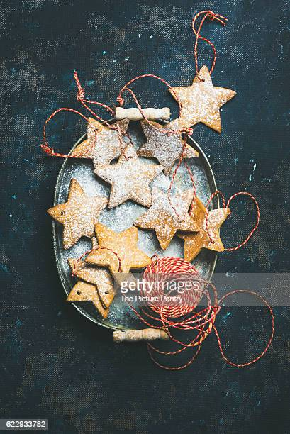Christmas holiday star shaped gingerbread cookies for Christmas tree decoration with red ropes in vintage metal tray over dark blue shabby plywood background