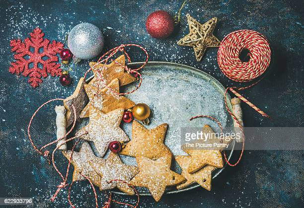 Christmas holiday star shaped gingerbread cookies for Christmas tree decoration, decorative snowflakes, balls and toys in metal tray over dark blue background