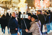 Christmas in France Adult couple use a selfie stick to take a selfie with the Christmas decorated city