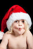 a cute baby wearing a santa hat ready to kiss