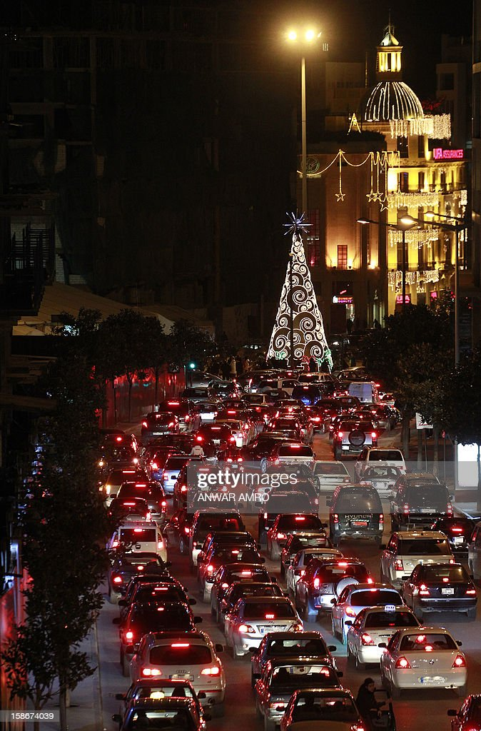 Christmas lights and a tree decorate a street as cars queue in traffic in the Lebanese capital Beirut on December 23, 2012. AFP PHOTO/ANWAR AMRO