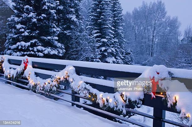 Lumières de Noël assis sur le pont en hiver avec la neige fraîche