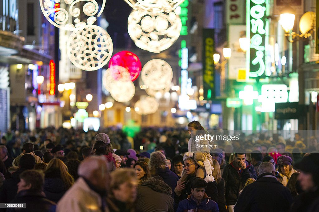 Christmas lights illuminate shoppers in a crowded shopping street in central Madrid, Spain, on Saturday, Dec. 29, 2012. Spain's economic activity kept falling in the fourth quarter, Bank of Spain says. Photographer: Angel Navarrete/Bloomberg via Getty Images