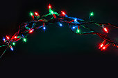 Multi colored stings of Christmas lights over black background