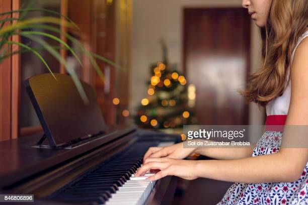 Christmas. Little girl playing the piano at home with the christmas tree in background