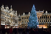 Night view of the crowded christmas market at Grand Place in Brussels, Belgium. Illuminated gothic buildings and christmas tree.