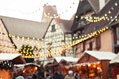 christmas market blurred background, people walking in cozy decorated street with garlandes and wooden houses of shops