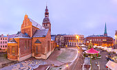 Decorated and illuminated Christmas tree, Christmas Market and the Cathedral of Saint Mary at Cathedral Square, Doma laukums, Riga, Latvia. Aerial panoramic view