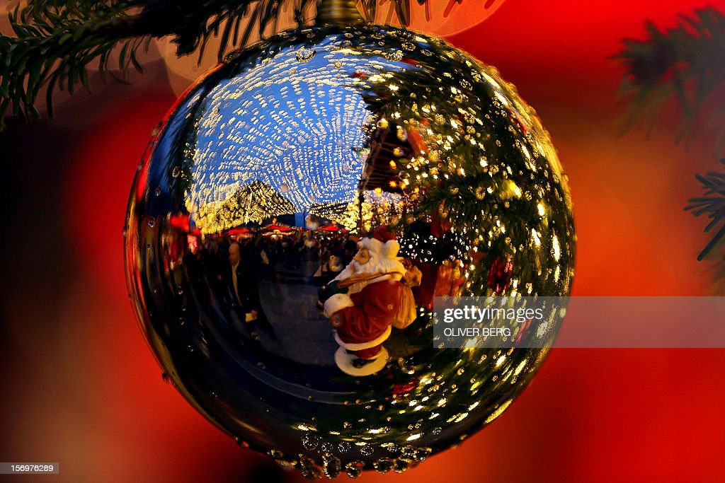 A christmas market scenery is reflected in a christmas ball in Cologne, western Germany, on November 26, 2012.