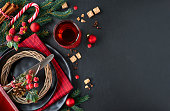 Christmas menu concept on dark stone slate background. Black plates and vintage cutlery with Christmas decorations in green, red and orange. Space for your text on the stone.