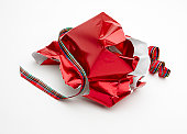 torn Christmas gift wrap and ribbon shot on white backgriound with soft shadow and room for copy