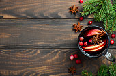 Christmas Mulled Wine with Apple and Cranberries. Holiday Concept Decorated with Fir Branches, Cranberries and Spices. Top View Flat Lay Copy Space.