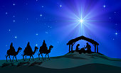 Representation of Christmas Nativity scene. Holy Family figurines are under a hut and three Wise Men on camels figurines coming in the desert, in silhouette style. In the background, blue starly sky a