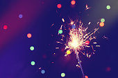 christmas, new year abstract background with sparkler, colorful bokeh, holiday theme