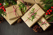 Christmas or New Year presents wrapped in natural coloured paper and decorated with traditional Xmas twine and fir twigs on a dark background