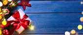 Christmas or New Year gift with festive fir tree on blue table at night