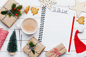 Cup of hot cocoa, holiday decorations, gift, present, miniature fir tree and notebook with to do list on white wooden table from above. Christmas or winter planning concept. Flat lay style.
