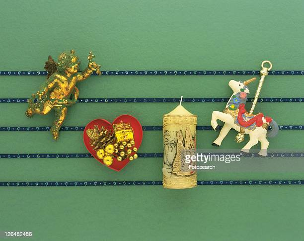 Christmas ornaments on blue lines, green background, high angle view