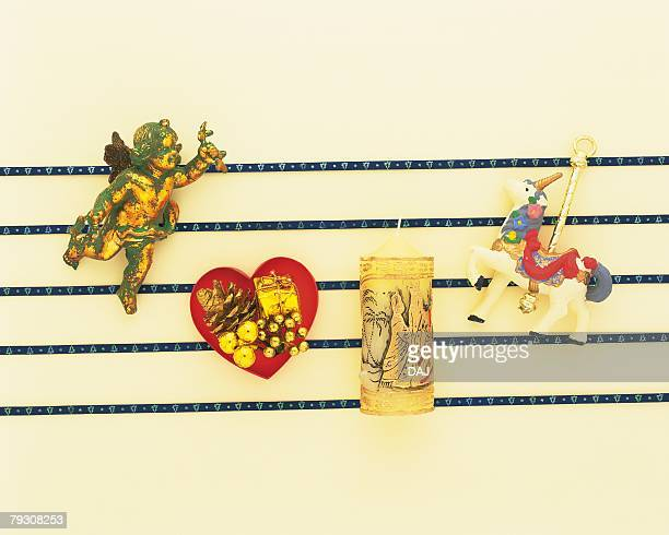 Christmas ornaments on blue lines, white background, high angle view