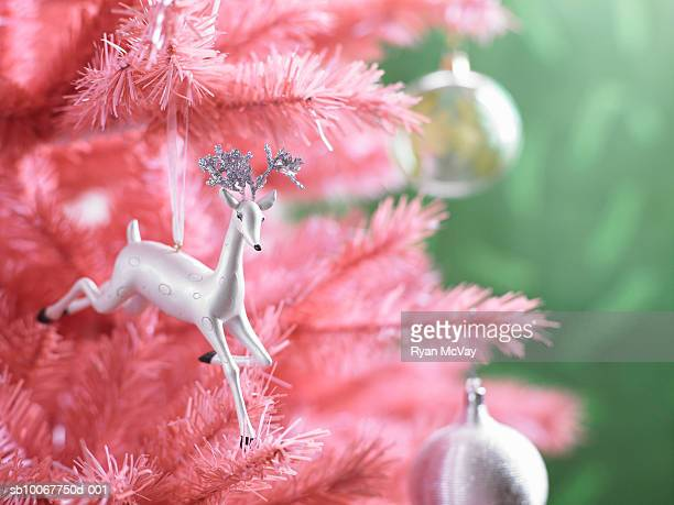 Christmas ornaments on pink Christmas tree, close-up
