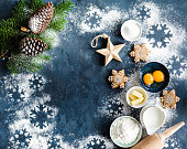Christmas/New Year food background. Baking ingredients, snowflake cookies, Christmas decoration. Making festive New Year sweets. Flour, rolling pin, gingerbread, milk, eggs. Space for text. Top view