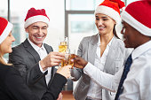 Happy colleagues in Santa caps toasting with champagne at corporate party
