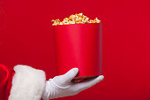 Christmas. Photo of Santa Claus gloved hand With a red bucket with popcorn, on a red background.