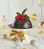 Christmas pudding decorated with holly and berry. Toned image. Traditional Christmas food.