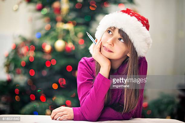 Christmas portrait of a little girl writing letter to santa