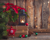 Christmas postcard with Poinsettia on the old books with fir tree, cones and toys balls and burning lantern. Toned.