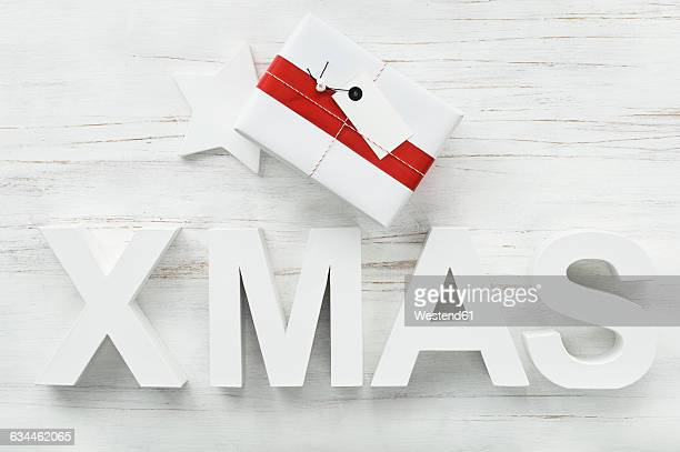 Christmas present and Christmas decoration with star and letters building the word Xmas