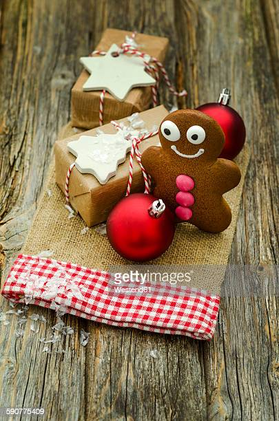 Christmas present, gingerbread man and two red Christmas baubles