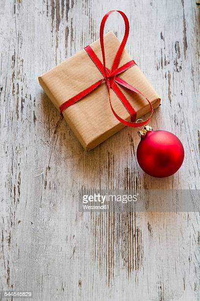 Christmas present with red Christmas bauble on wood