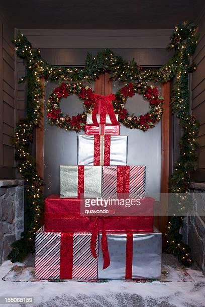 Weihnachten Geschenke vor Schnee Tür mit Kranz und Blumenkranz