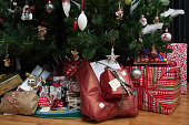 close up shot of christmas presents under a christmas tree