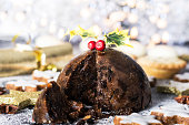 Christmas pudding, mince pies and Christmas cookies on a bed icing sugar with bokeh lights in the background.