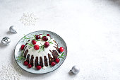 Christmas Pudding, Fruit Cake decorated with icing and cranberries on white table, copy space. Homemade traditional christmas dessert - Christmas Pudding.
