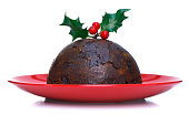 Photo of a steamed Christmas pudding with holly on top isolated on a white background.