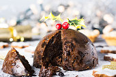 Christmas Pudding, mince pies and Christmas cookies. Christmas scene and decorations in the background.