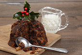 christmas pudding on a cutting board with cream and a spoon