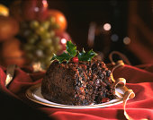 Christmas Pudding decorated with holly leaves  on red background