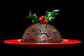 Photo of a Christmas pudding with holly on top isolated on a black background.