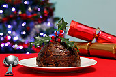 Photo of a Christmas pudding with holly on top plus tree and crackers in the background.