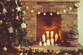 Decorated Christmas tree in front of the fireplace with various candles, pine cones and baubles, selective focus; dark vintage style toned photo