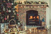 Beautiful Christmas setting, decorated fireplace with woodburner, lit up Christmas tree with baubles and ornaments, lantern, stars and garlands, selective focus