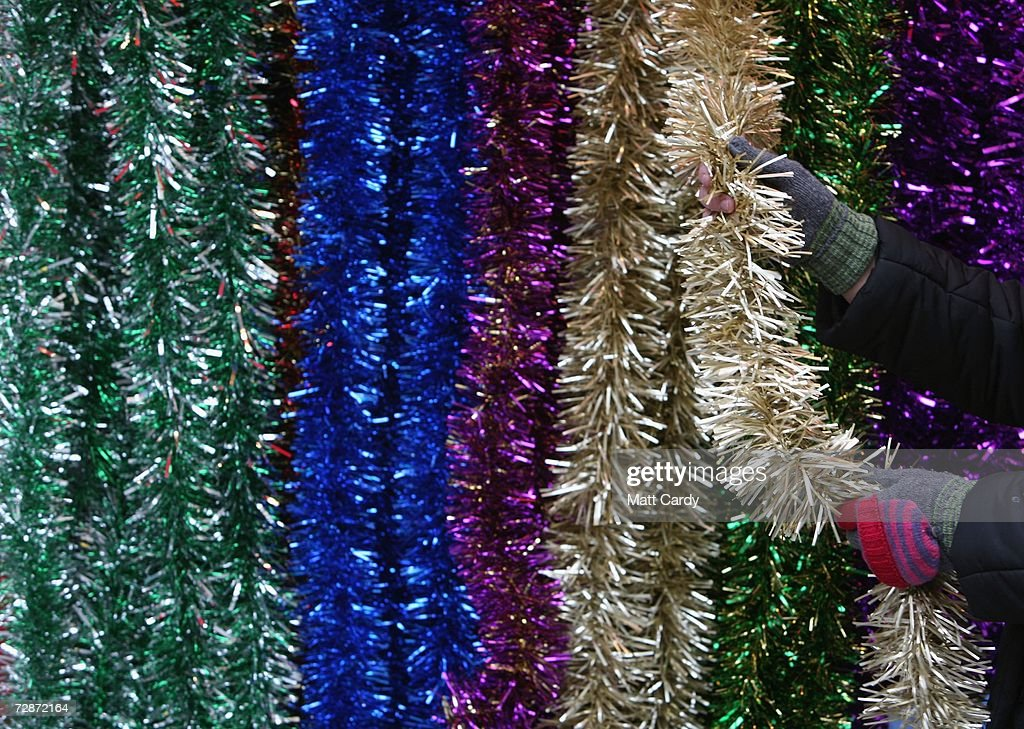 A Christmas shopper buys some tinsel on the high street on December 23, 2006 in Bath, England. With just two days to go before Christmas, the streets are full of people as they are finishing their last-minute Christmas shopping.