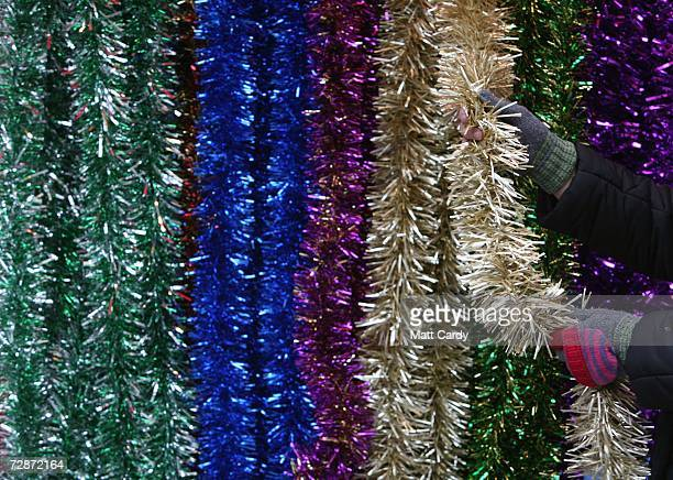 Christmas shopper buys some tinsel on the high street on December 23 2006 in Bath England With just two days to go before Christmas the streets are...