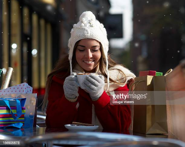 Christmas shopper holding cup of coffee.